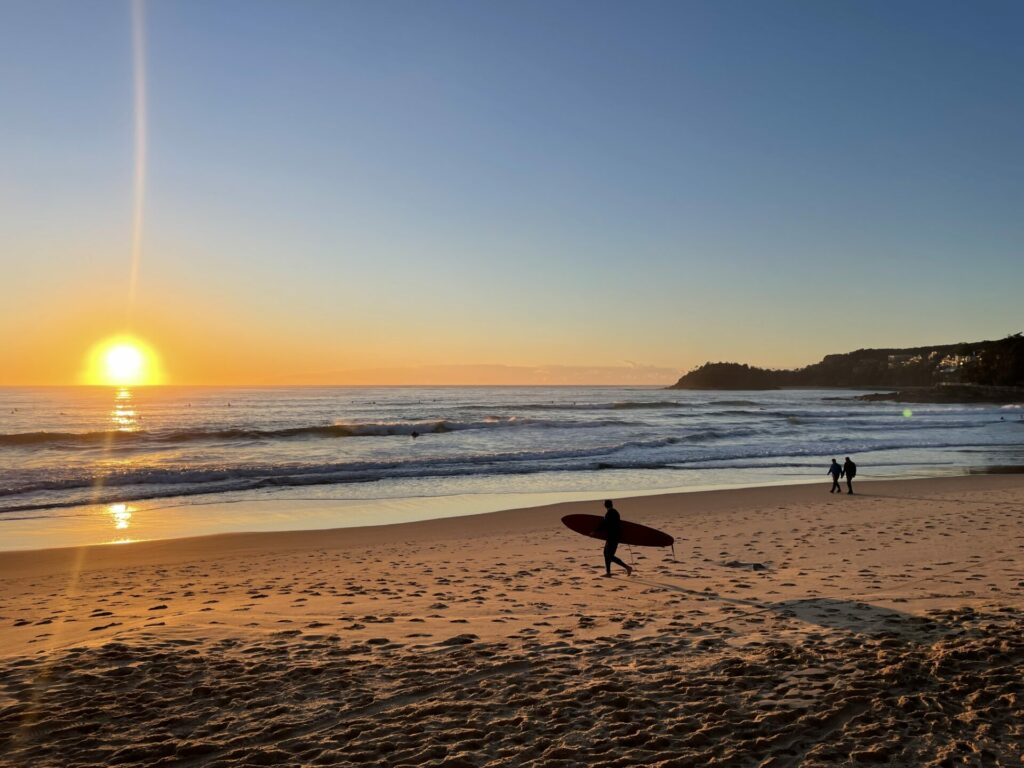 Sunrise over a beach with a surfer in the foreground.